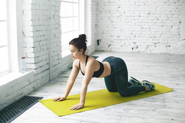 Atlética jovem iogue feminino em roupa de esporte preto da moda, aquecendo a espinha, fazendo vaca asana. garota flexível praticando backbends de ioga em uma sala espaçosa com uma parede de tijolos brancos para seu texto Foto gratuita