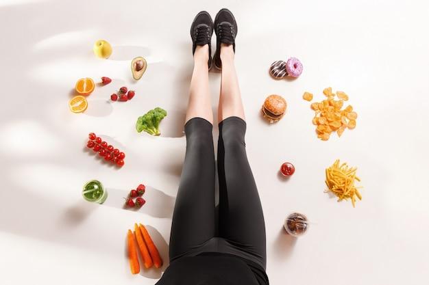 Atlética menina com comida saudável no chão Foto gratuita