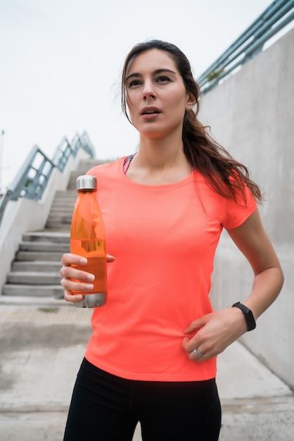 Atlética mulher bebendo água após o treino Foto gratuita