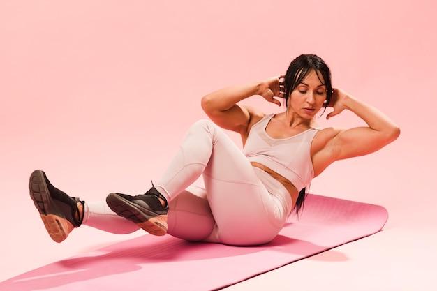 Atlética mulher com roupa de ginástica fazendo abdominais na esteira Foto gratuita