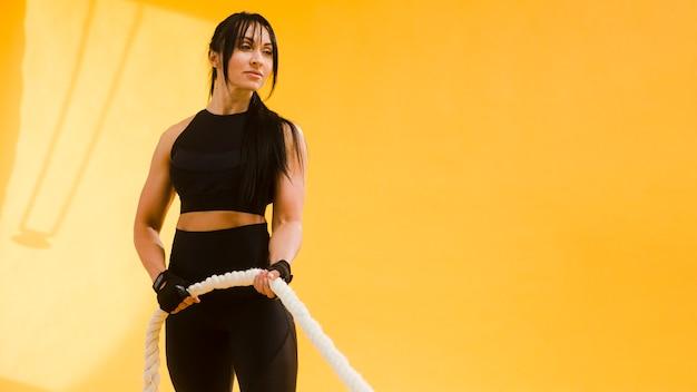 Atlética mulher em roupa de ginástica com corda Foto gratuita