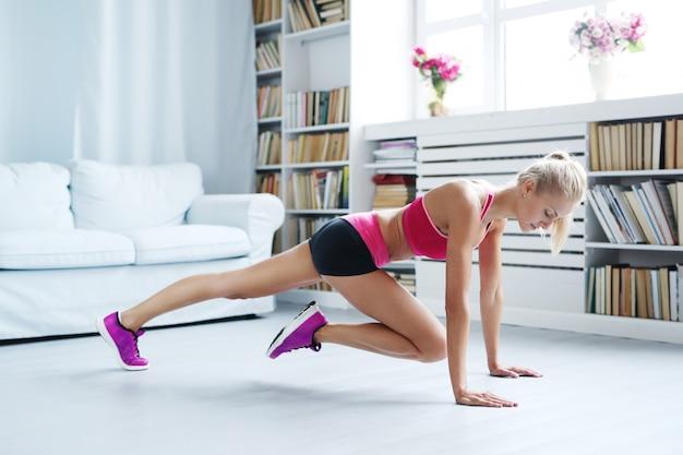 Atlética mulher exercitando em casa, treino Foto gratuita