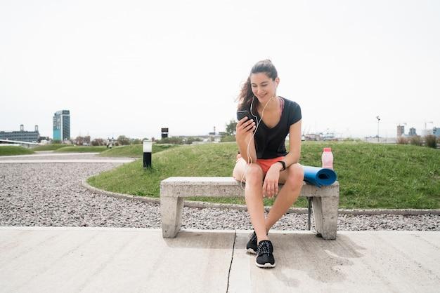 Atlética mulher usando seu telefone Foto gratuita