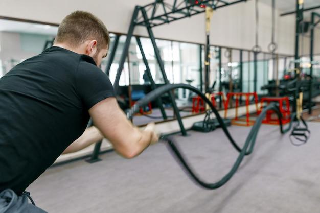 Atlético barbudo homem musculoso exercitando na academia Foto Premium