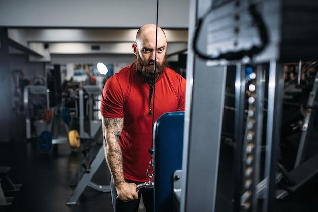 Atlético do sexo masculino no sportswear, treinando na máquina de exercícios no ginásio. homem barbudo fazendo exercícios no clube esportivo, estilo de vida saudável Foto Premium