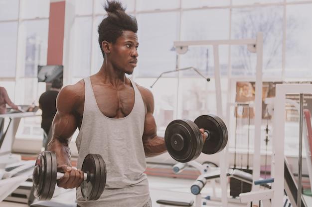 Atlético homem africano malhando com halteres na academia Foto Premium