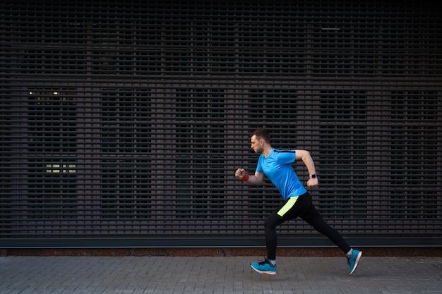 Atlético homem correndo na rua urbana contra fundo cinza Foto gratuita