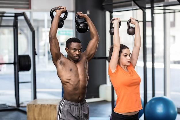 Atlético homem e mulher malhando na academia crossfit Foto Premium