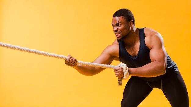 Atlético homem em roupa de ginástica, puxando a corda Foto gratuita