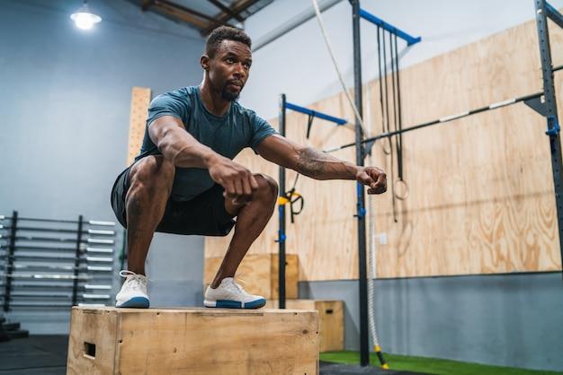 Atlético homem fazendo exercício de salto de caixa. Foto Premium