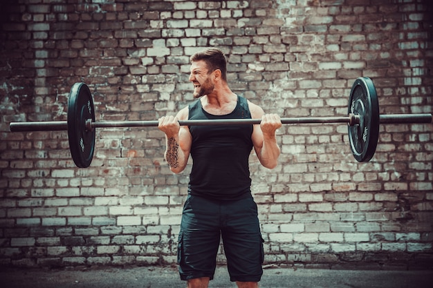 Atlético homem malhando com um barbell. força e motivação. exercício de bíceps. Foto Premium
