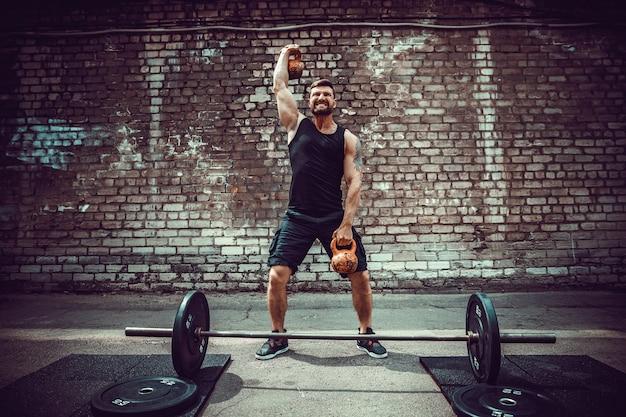 Atlético homem malhando com um kettlebell. força e motivação Foto Premium