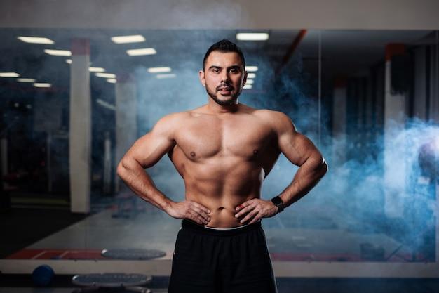 Atlético homem posando, exibindo seus músculos no ginásio Foto Premium