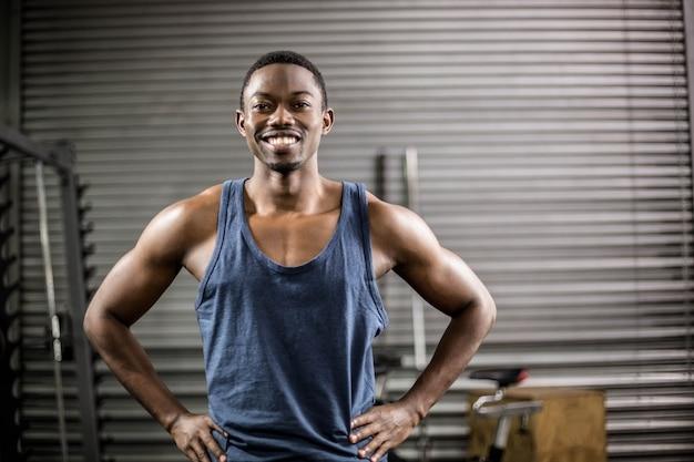 Atlético homem sorrindo para a câmera no ginásio Foto Premium