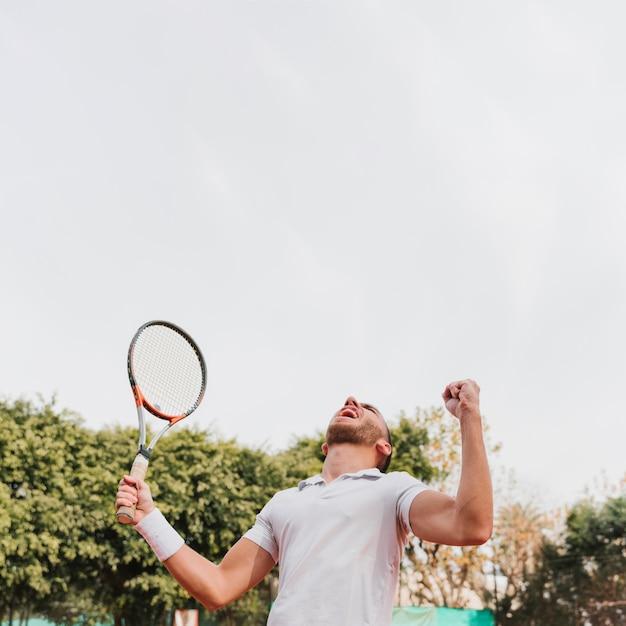 Atlético jovem rapaz ganhando um jogo de tênis Foto gratuita
