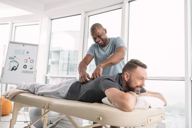 Atmosfera relaxante. homem feliz e encantado sorrindo enquanto faz uma massagem nas costas de seu paciente Foto Premium