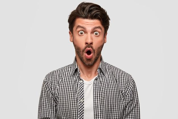 Atônito funcionário do escritório, tem olhos grandes e boca aberta, rosto surpreso, vestido com camisa xadrez, encostado na parede branca. conceito de pessoas, reação e choque. omg, o que eu vejo! Foto gratuita