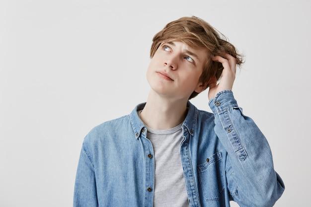 Atordoado homem de cabelos loiros de olhos azuis, olha com expressão confusa, tenta se lembrar de algo importante. jovem sonhador pensativo posa dentro de casa Foto gratuita