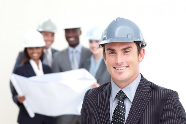 Atraente arquiteto masculino com sua equipe em segundo plano Foto Premium