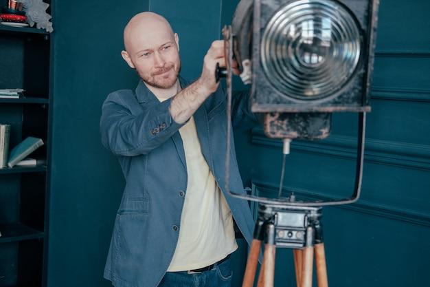 Atraente, careca adulto, com, barba, em, paleto, olhar, antigas, dispositivo elétrico clarão, luz vídeo Foto Premium