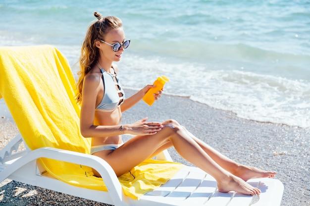 Atraente, encantador, mulher, em, swimsuit, e, óculos de sol, aplicando, loção sol, ligado, dela, pernas Foto gratuita