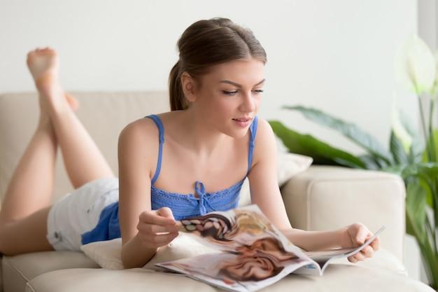 Atraente garota lendo revista deitada no sofá em casa Foto gratuita