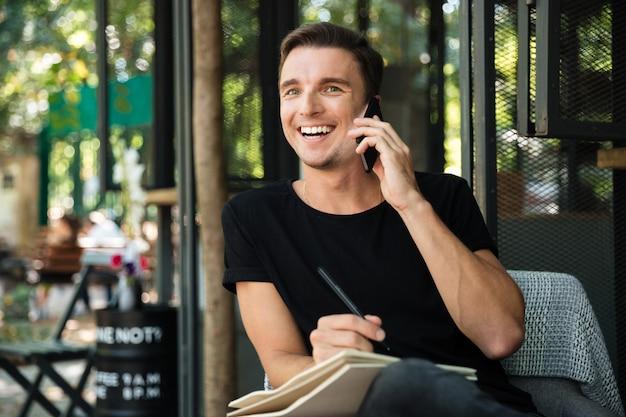 Atraente homem rindo falando no celular enquanto está sentado Foto gratuita