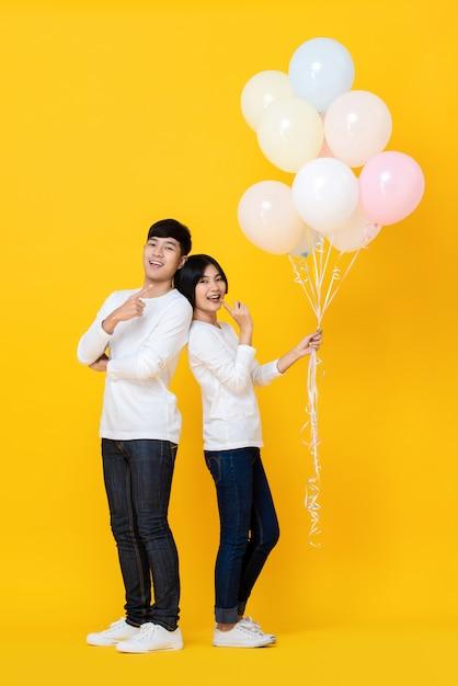 Atraente jovem amante asiática segurando balões coloridos Foto Premium