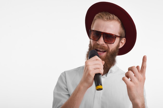 Atraente jovem barbudo showman usando óculos escuros elegantes e chapéu segurando o microfone e levantando o dedo indicador enquanto anuncia a apresentação do cantor popular Foto gratuita