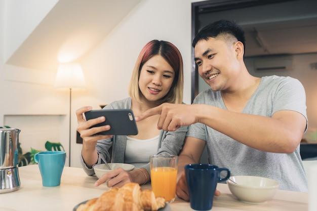 Atraente jovem casal asiático distraído na mesa com jornal e telefone celular Foto gratuita