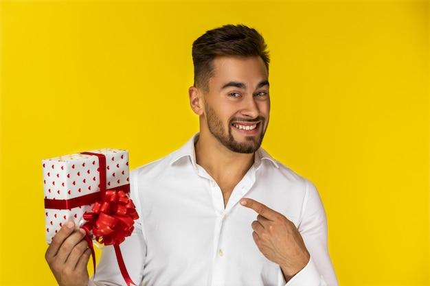 Atraente jovem europeu na camisa branca está mostrando um presente embalado Foto gratuita