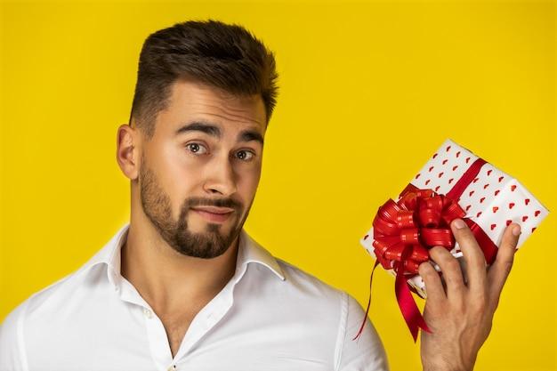 Atraente jovem europeu na camisa branca está segurando um presente Foto gratuita