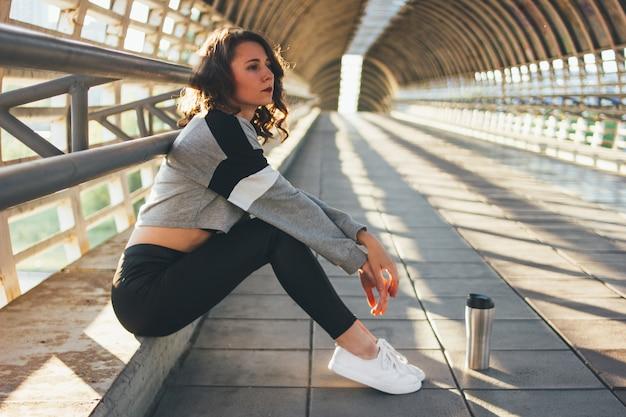 Atraente jovem morena morena dançarina ginasta sentado e descansar com copo térmico na ponte Foto Premium