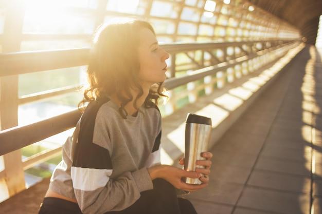 Atraente jovem morena morena dançarina ginasta sentado e descansar com copo thermo Foto Premium