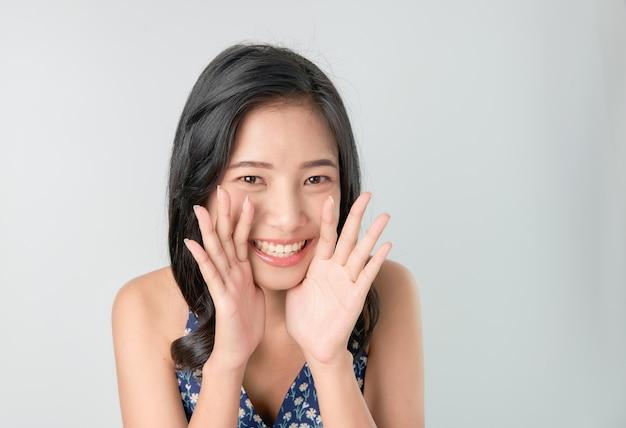 Atraente jovem mulher asiática anunciando com as mãos na boca e contando um segredo Foto Premium