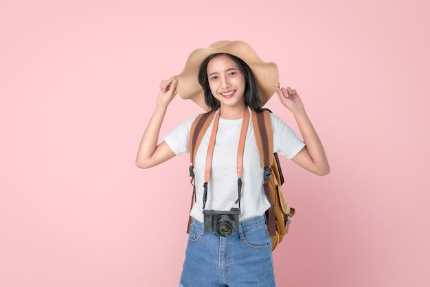 Atraente jovem mulher asiática viajante tocando chapéu na cabeça Foto Premium