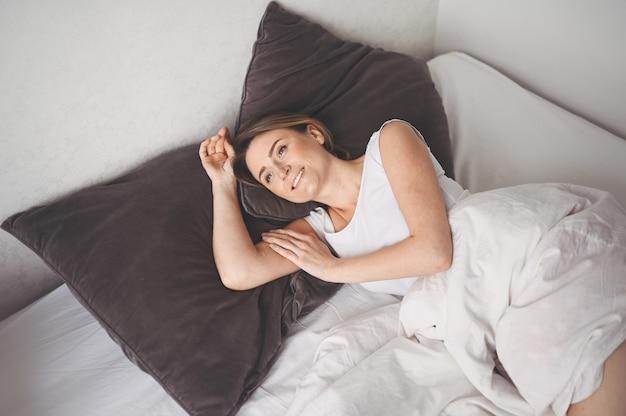 Atraente jovem sorridente, estendendo-se na cama, acordando sozinho feliz conceito, acordado após um sono saudável na confortável cama confortável e colchão desfrutar de bom dia Foto Premium