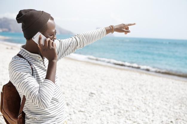 Atraente jovem viajante afro-americano em roupas da moda, apontando algo no mar enquanto fala no seu celular contemporâneo, viajando sozinho na cidade estrangeira. pessoas e férias de verão Foto gratuita