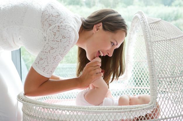Atraente, mãe jogando, com, bebê berço Foto Premium
