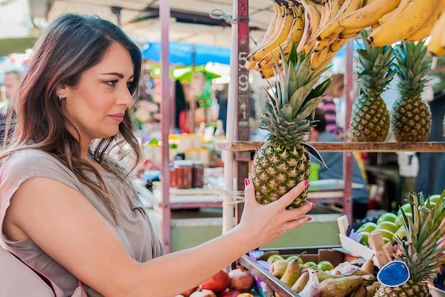 Atraente mulher comprando no mercado verde. closeup portrait jovem mulher bonita pegando, escolhendo frutas, abacaxis. expressão de expressão positiva emoção que sente um estilo de vida saudável Foto gratuita