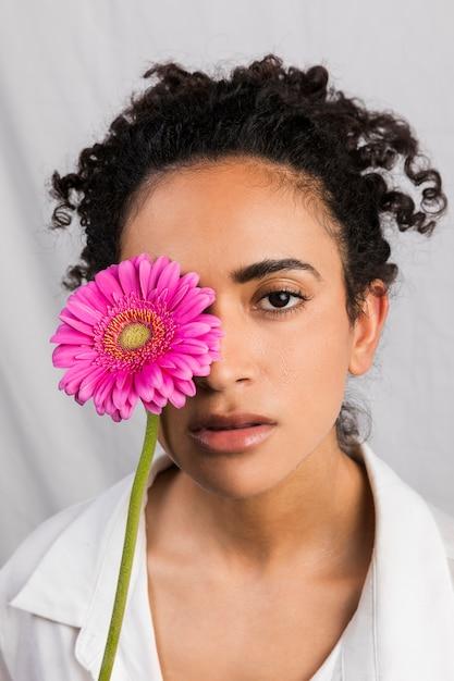 Atraente, mulher étnica, coberta, olho, com, flor Foto gratuita
