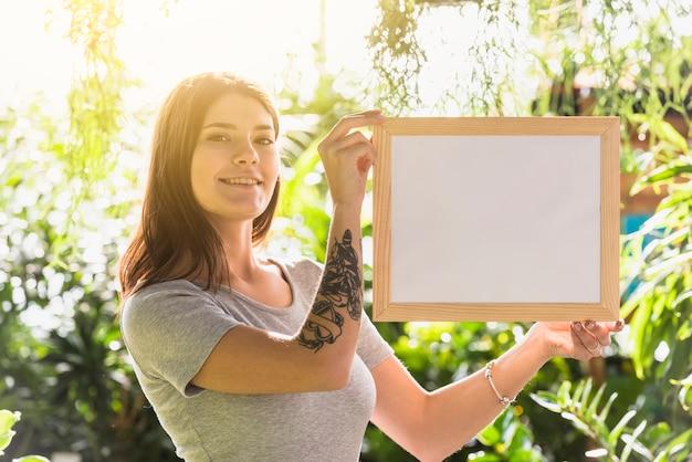 Atraente, mulher feliz, segurando, photo frame, entre, plantas Foto gratuita