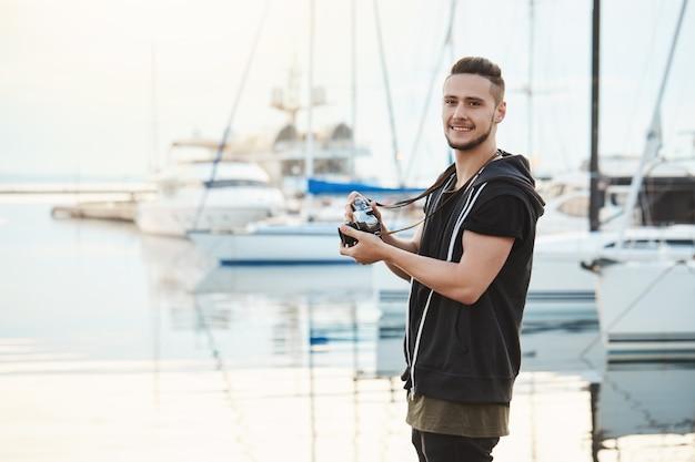 Atraente namorado focado em seu hobby durante passeio com a namorada. retrato de cara em pé no porto perto de iates, segurando a câmera, olhando de lado enquanto procurava por grande tiro. Foto gratuita