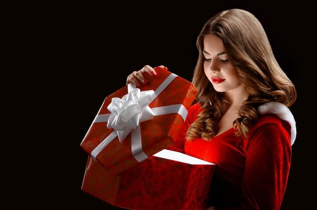 Atraente snow maiden abre um grande presente vermelho para o ano novo Foto gratuita