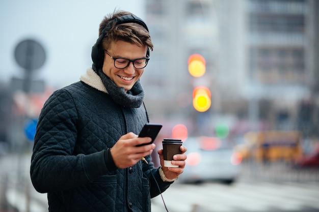 Atraente, sorrindo, sujeito, escutar música, em, fones, usando, seu, telefone móvel Foto gratuita