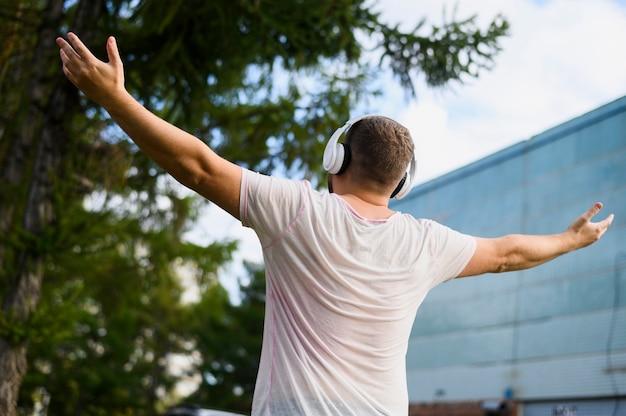Atrás de um jovem com as mãos levantadas Foto gratuita