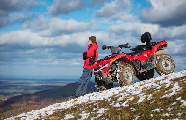 Atv moto perto do homem olha para a distância na encosta da montanha de neve na frente do céu azul nublado com espaço da cópia Foto Premium