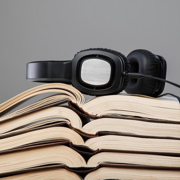 Audiobooks, fones de ouvido na pilha de livros Foto Premium