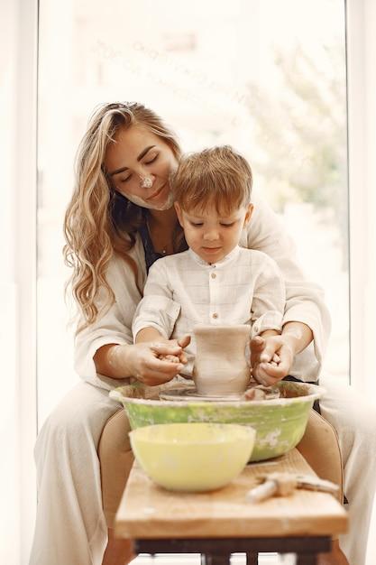 Aulas de cerâmica. jovem mãe caucasiana ensinando seu filho. filho fazendo panela de barro na roda de oleiro. Foto gratuita