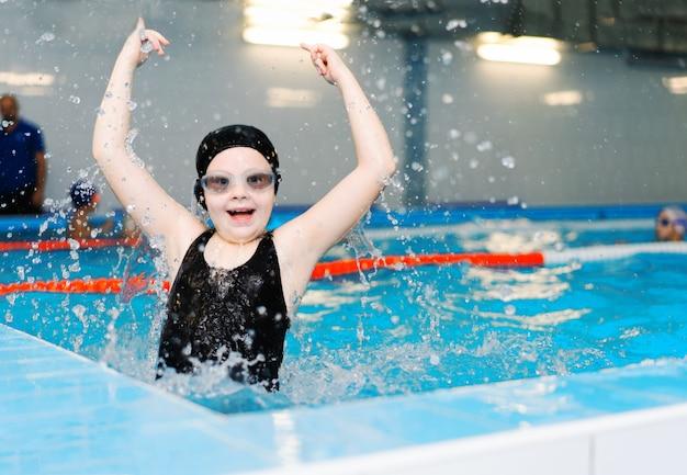 Aulas de natação para crianças na piscina - linda menina de pele clara nada na água Foto Premium